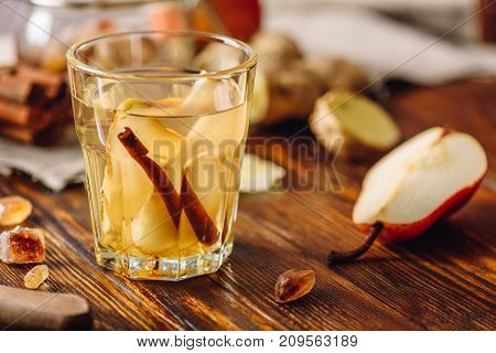 Glass of Water Infused with Pear Cinnamon Stick Ginger Root and Some Sugar. Ingredients Scattered on Wooden Table.