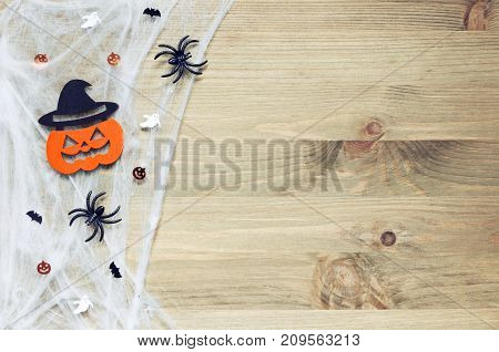 Halloween background. Spider web spiders and smiling jack decorations as symbols of Halloween on the wooden background. Halloween background with Happy Halloween concept. Halloween holiday background