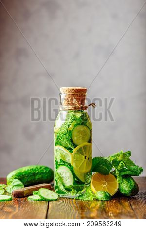 Bottle of Water Infused with Sliced Lemon Cucumber and Mint Leaves. Ingredients and Knife on Table. Copy Space on the Top. Vertical Orientation.