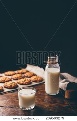 Glass of Milk with Bottle and Oatmeal Cookies on Parchment Paper. Copy Space on the Top.