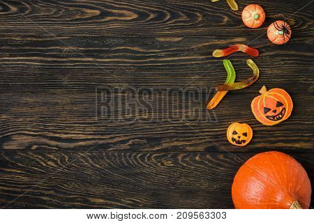 Halloween holiday background with pumpkins candy and spider. View from above.