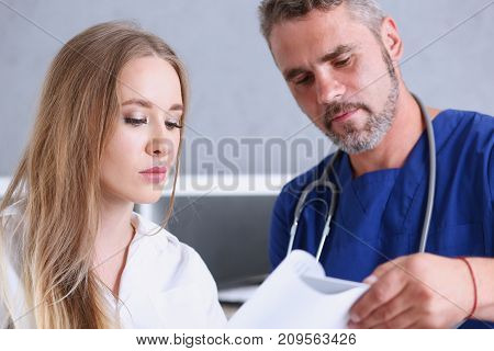 Concerned handsome doctor communicate with patient holding silver pen and showing pad. Physical agreement signature disease prevention consent sign 911 prescribe remedy healthy lifestyle concept