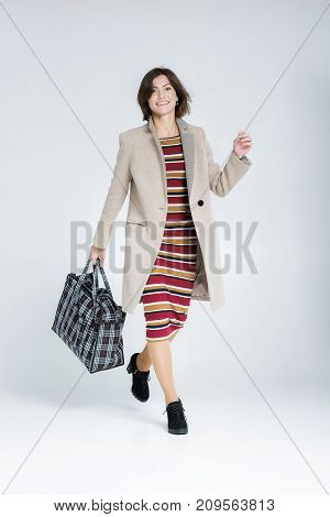 attractive woman with a big shopping bag on a gray background