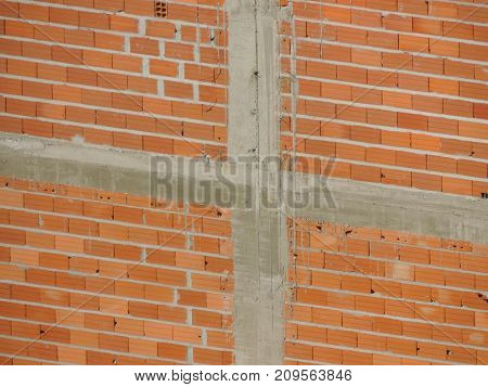 Brick wall with exposed concrete bars under construction