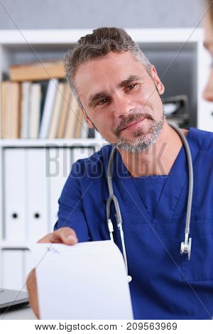 Male medicine doctor in blue uniform hold and give prescription to patient closeup. Panacea and life save prescribe treatment legal drug store contraception concept empty form ready to be used