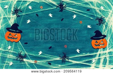 Halloween background with spider web spiders and smiling jack decorations as symbols of Halloween on the dark green background. Halloween background with Halloween holiday concept. Halloween still life