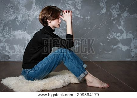 The young sad woman sitting on floor at home