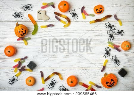 Halloween holiday background with candy cookies and spiders. View from above.
