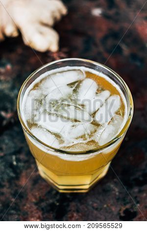 Ginger beer in glass on black rustic surface.