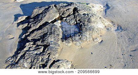 Corazón tallado en la piedra sobre la arena
