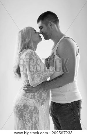 Beautiful pregnant couple in love on the background. Hands of husband on the tummy of his pregnant wife. Young man tenderly stroked pregnant belly of his wife. Husband kissing pregnant belly. poster