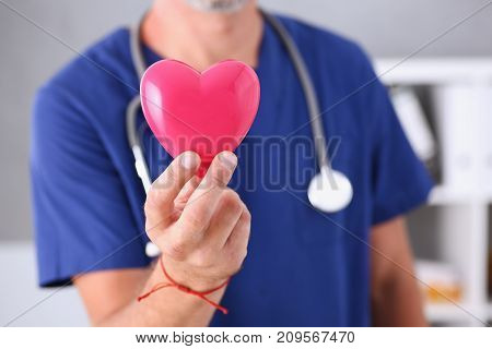 Male doctor wearing blue uniform hold in arms red toy heart closeup. Cardio therapeutist student education CPR 911 life save physician make cardiac physical pulse rate measure arrhythmia