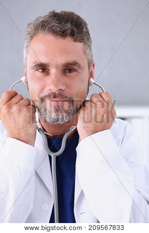 Handsome mature smiling male doctor hold in arms stethoscope going to listen patient. Tool shop or store physical and disease prevention er consultant 911 pulse measure healthy lifestyle