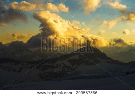 A sunset panorama of the elbrus and part of the Caucasian ridge with orange clouds and a cracked glacier at the bottom