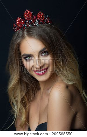 portrait of beautiful young girl with makeup and hairdo with crown on head on black background