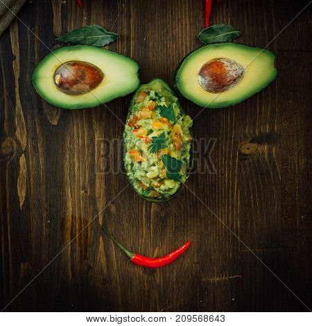 Funny food face made from avocado and guacamole dip