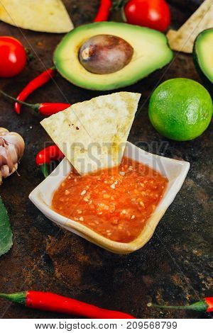 Hot mexican salsa whith the nacho chips surrounded by ingredients - tomatoes, chili peppers, lime
