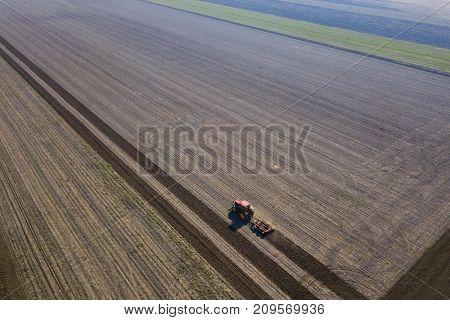 Farmer with tractor preparing soil with seedbed cultivator.