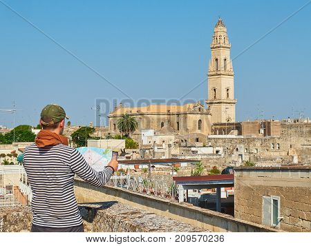 Traveler with a map in his hans in front of Lecce rooftop view with the Campanile bell tower of Cattedrale metropolitana di Santa Maria Assunta cathedral in background. Lecce Puglia Italy.