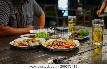 Dinning table in restaurant including Thai food,papaya salad etc. and two glasses of beer  with man sit in the opposite