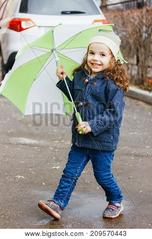 Little girl playting on the rainy street with green umbrella