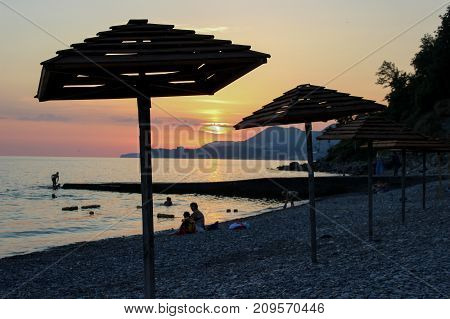 two beach umbrella, sunset on the beach, evening beach, two umbrellas made of wood, beach tents, people on the coast