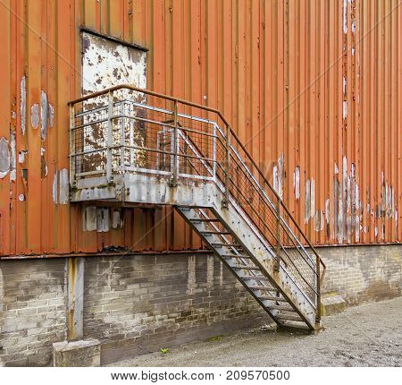 weathered rundown industrial scenery with old corroded stairway and door