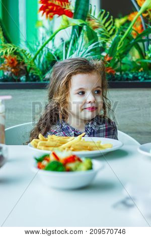 Kid girl in a restaurant eating fast food