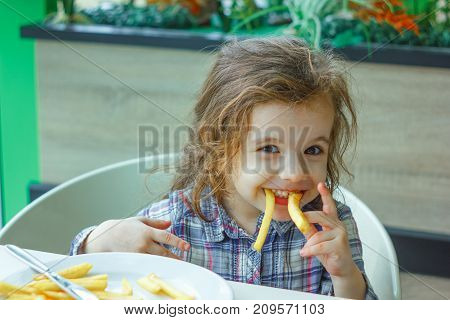 Little girl play with the french fries in a restaurant