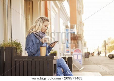 Pretty woman is sitting on the outdoor terrace and have breakfast. freelance