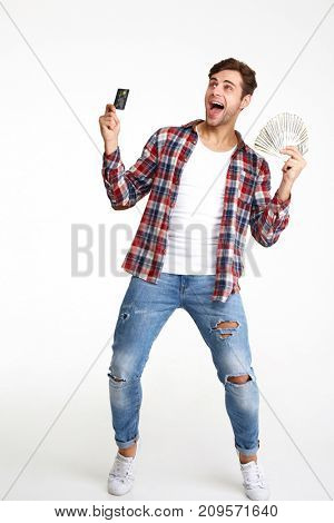 Full length portrait of a happy smiling man holding bunch of money banknotes and showing credit card isolated over white background