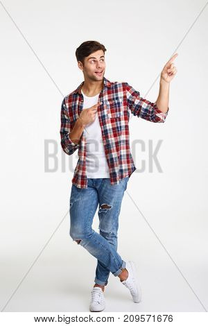 Full length portrait of a happy excited man pointing two fingers away at copy space isolated over white background
