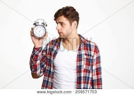 Portrait of a restless man holding and looking at alarm clock isolated over white background