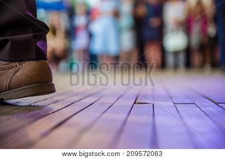men's foot in the shoes and dance floor in the open area