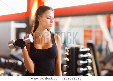 Young beautiful woman exercising with a dumbbell in a gym. A smiling girl enjoys the process of training. She works hard.