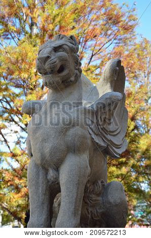 ASHEVILLE, NC - October 12, 2017 A winged lion statue against the fall trees in the background sits along the entrance of the Grove Arcade Building.