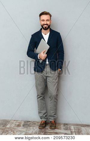 Full length image of smiling bearded man in business clothes holding laptop computer and looking at the camera over gray background