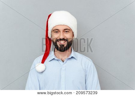 Smiling Bearded man in business clothes and christmas hat looking at the camera over gray background