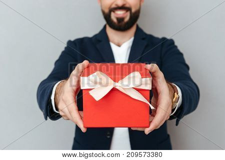 Cropped image of smiling bearded man in business clothes presents a gift at camera over gray background
