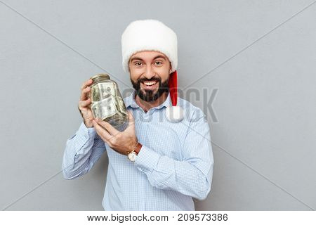 Happy Bearded man in business clothes and christmas hat holding arm with money and looking at the camera over gray background