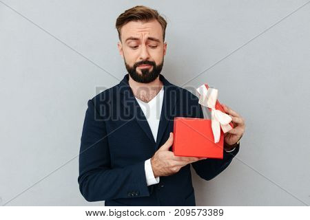 Image of Surprised bearded man in business clothes opening gift over gray background