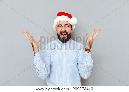 Confused screaming Bearded man in business clothes and christmas hat looking up over gray background
