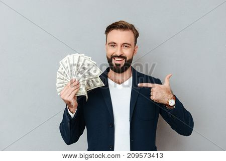 Smiling bearded man in business clothes holding money and pointing on their while looking at the camera over gray background