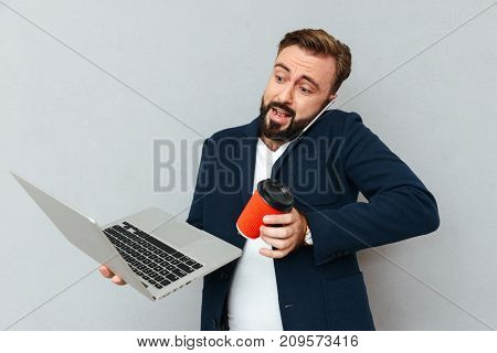 Busy surprised bearded man in business clothes talking by smartphone and using laptop computer while holding cup of coffee in hand over gray background