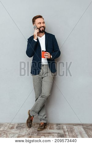 Full length image of happy bearded man in business clothes talking by smartphone while holding cup of coffee and looking away over gray background