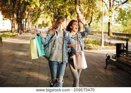 Photo of two beautiful woman friends holding shopping bags while walking on street