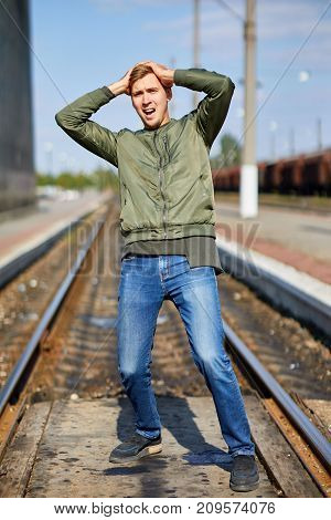 A young man in a panic stands on the rails holding his head