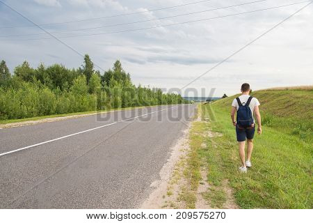 A man walking along the grass parallel to the road against the background of the sky and greenery