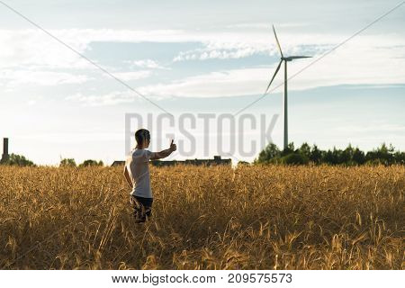A man standing in a wheat field looking at a wind generator