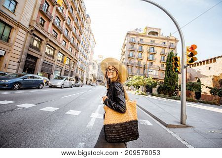 Woman tourist in hat crossing the street during the morning light in Barcelona city